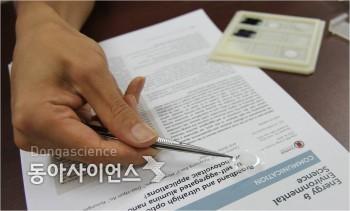 연구팀이 핀셋으로 이번에 개발한 광안개 메타 필름을 보이고 있다.  - 신선미 기자, vamie@donga.com 제공